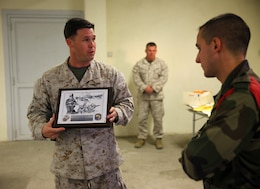 Capt. T. D. McAbee, the air operations officer for Special-Purpose Marine Air-Ground Task Force Crisis Response, presents a plaque to a company commander with the 2nd Foreign Infantry Regiment of France's 6th Light Armored Brigade Oct. 31, 2013, at Camp des Garrigues, France. The event was part of a week-long bilateral training exercise between U.S. Marines with SP-MAGTF Crisis Response and French Legionnaires. SP-MAGTF Crisis Response is a self-mobile, self-sustaining force capable of responding to a range of crises to protect both U.S. and partner-nation security interests in the region, as well as strengthening partnerships throughout the U.S. European Command and U.S. Africa Command area of responsibility. (U.S. Marine Corps photo by Cpl. Michael Petersheim)