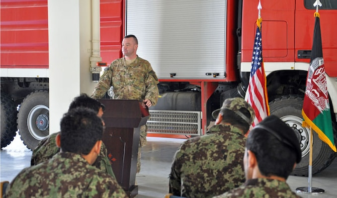 Master Sgt. Jeffery Hackworth addresses graduates of the first Afghan Fire Instructor Course during a ceremony Oct. 31, 2013 at Kabul International Airport, Afghanistan. The five-day class was developed by NATC-A advisors and graduated 13 Afghan Air Force and Afghan National Army firefighters as certified instructors. The graduates can now certify additional firefighters at their home fire stations. Hackworth is the NATO Air Training Command-Afghanistan fire adviser.