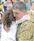 A Soldier with Co. F, 1st Avn. Regt. holds his daughter following the unit's Oct. 24 welcome home ceremony at Marshall Army Airfield.  Photo by: Sgt. Keven Parry, 1ST CAB.