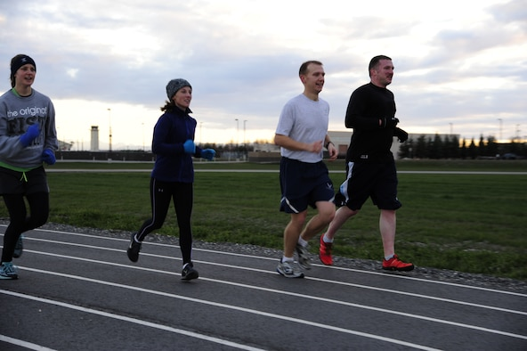 Participants in a running group make their way around the outdoor track during a workout Oct. 25, 2013, Eielson Air Force Base, Alaska. The running group is open to anyone and typically meets at noon on Fridays. For additional information on running or other fitness activities, visit the fitness center or call the Health and Wellness Center at 377-9355. (U.S. Air Force photo by Senior Airman Zachary Perras)