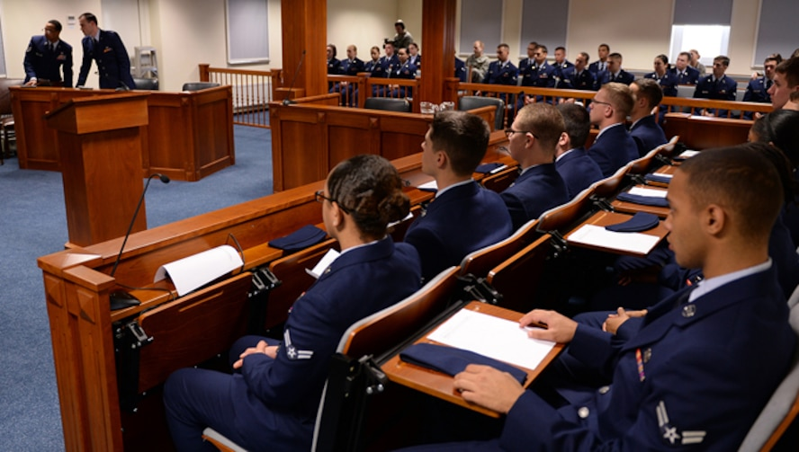 """Airmen fill the 52nd Fighter Wing legal office courtroom during the """"Got Consent?"""" training Oct. 24, 2013. """"Got Consent?"""" is an interactive training session that allows first-term Airmen to participate as jurors in a sexual assault case. Legal office personnel broadcasted pre-recorded interviews from the plaintiff and defendant before the jury panel as part of the training's program. (U.S. Air Force photo/Daryl Knee)"""