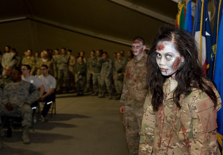 Staff Sgt. Soleil Tucker, 376th Expeditionary Civil Engineer Squadron operations management, shows off her zombie impersonation during a 376th Air Expeditionary Wing awards ceremony at Transit Center at Manas, Kyrgyzstan, Oct. 31, 2013. Tucker is deployed out of Travis Air Force Base, Calif., and is a native of Quezon City, Philippines. (U.S. Air Force photo/Staff Sgt. Krystie Martinez)