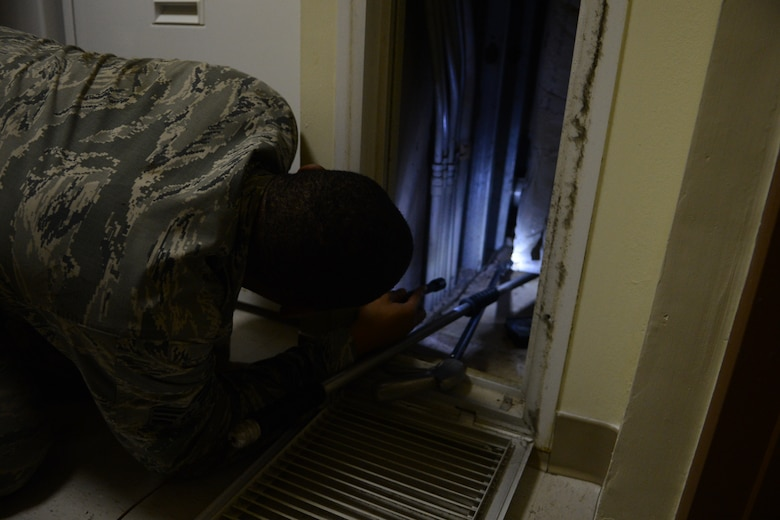Senior Airman Terrance Stewart, 36th Civil Engineering Squadron NCO in charge of pest management, removes a deceased animal from a vent Oct. 28, 2013, on Andersen Air Force Base, Guam. When animals are found deceased, the Entomology Airmen dispose of the carcasses cautiously to prevent the spread of disease. (U.S. Air Force Photo by Airman 1st Class Emily A. Bradley/Released)