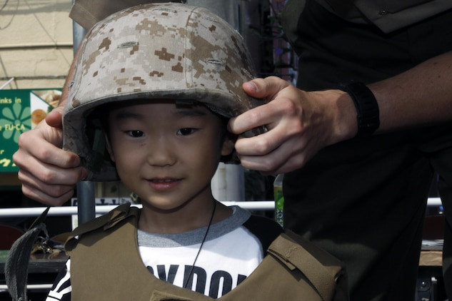 A Marine helps dress a local child for a photo with Marines and sailors during the 55th annual Iwakuni Festival Oct. 16. 12 Marines and sailors from Marine Aviation Logistics Squadron 12 and Marine Aircraft Group 12 volunteered for the event.