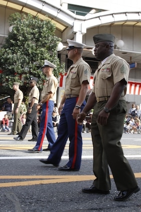 Several Marines and sailors walk as part of the parade during the 55th annual Iwakuni Festival in downtown Iwakuni Oct. 16. Twelve Marines and sailors with Marine Aviation Logistics Squadron 12 and Marine Aircraft Group 12 volunteered for the festival, donning a variety of different uniforms and gear. A tent was set up for the service members to shake hands and take pictures with the local community.