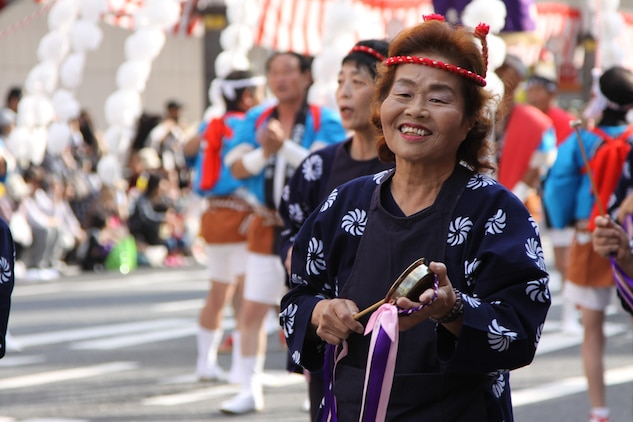 A performer smiles during the parade at the 55th annual Iwakuni Festival Oct. 16 held in downtown Iwakuni. The parade occupied the road with approximately 700 performers under 14 groups from Iwakuni city hall, JMSDF and local businesses. To accommodate the festival approximately 400 meters from Route 188 was closed to vehicle traffic.