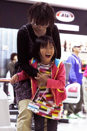 Murakami Naho, 9, a competitive disabled athlete screams with joy and holds onto her mother after bowling a spare at the Strike Zone here Sunday. All of the competitors participated when taken to the bowling alley here, and they all received a medal at the end of the Special Olympics.