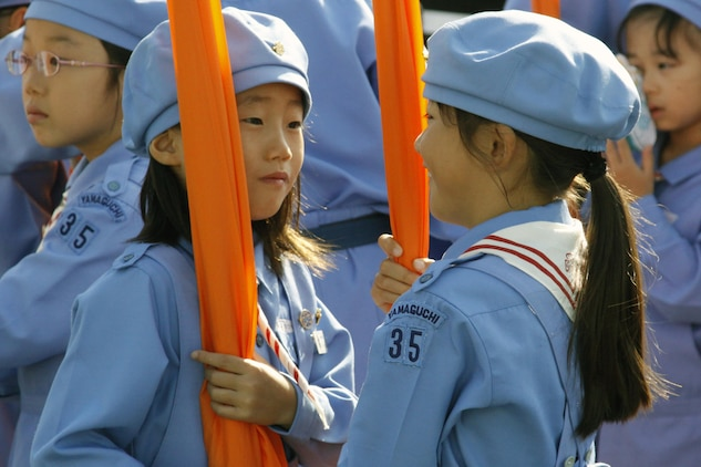 Two parade performers hold their banners during the opening ceremony at the 55th annual Iwakuni Festival Oct. 16 held in downtown Iwakuni. According to the event host, approximately 100,000 people permeated the streets of downtown Iwakuni to attend the festival, which was filled with live music, dancing, parades, vendors and food.
