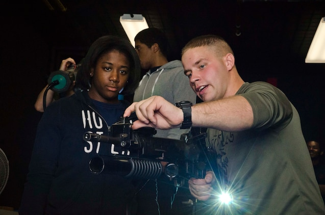 U.S. Marine Corps Pfc. Michael A. Lewis Jr., a Marine currently assigned to recruiter assistance at Marine Corps Recruiting Station Baltimore and a native of Baldwin, Md., shows Aisha Green, a member of RS Baltimore's Delayed Entry Program, how to sight in an M16A2 service rifle during a simulation at 4th Combat Engineer Battalion's headquarters in Parkville, Md., Oct. 12, 2013. Recruiters from RS Baltimore brought 35 members from their Delayed Entry Program to 4th CEB's Indoor Simulated Marksmanship Trainer (ISMT) facility in order to familiarize them with the Marine Corps and marksmanship training. (U.S. Marine Corps photo by Cpl. Bryan Nygaard/Released)