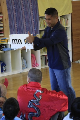 Chief F. B. Dizon, Station chapel religious programmer chief, shows an English alphabet book to children at Midoro Hoiken school Oct. 27. The chapel has been going to Midoro once a month for the past eight years to help Japanese children learn English and to teach the value of exchanging cultures. The chapel goes to Midoro on the fourth Thursday of every month unless a holiday makes it otherwise.