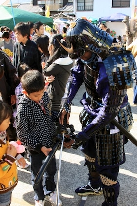Lance Cpl. Julias Hall, volunteer samurai, exchanges his kitana for a local japanese child's balloon sword during the samurai stage performance of the 22nd Kuragake Castle Festival in Kuga, Iwakuni City, Nov. 20. Event coordinators and local volunteers appreciated the Marines taking time out of their weekend to help reflect on such an important part of the local history.