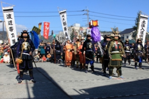 Japanese and American volunteer samurai form a platoon formation in front of the stage of the 22nd Kuragake Castle Festival in Kuga, Iwakuni City, Nov. 20. Event coordinators hope to broaden the spectrum of Marine volunteers over time, and in the near future, have a full squad of Marine volunteers during the event.