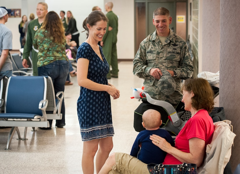 Sarah Hanks, wife of Senior Master Sgt. Justus Hanks, 437th Operations Support Squadron Aircrew Flight Equipment superintendent and Chief Master Sgt. Shawn Hughes, 437th Airlift Wing command chief, share a laugh with baby, Noah Hanks, while awaiting the return of Sarah's husband November 2, 2013 at Joint Base Charleston — Air Base, S.C. SMSgt Hanks was deployed with the 14th Airlift Squadron. (U.S. Air Force photo/Airman 1st Class Michael Reeves)