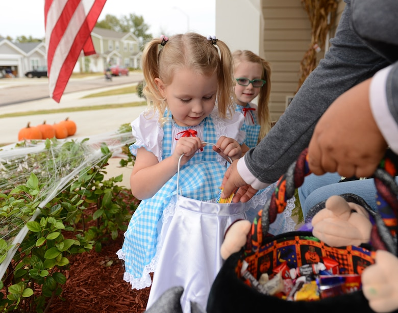 Sara, 4, and Kyleigh, 4, choose treat over trick while going door-to-door during Halloween, Shaw Air Force Base, S.C., Oct. 31, 2013. In addition to a week of Halloween-themed events offered on base, base-housing residents welcomed hundreds of trick-or-treaters Halloween night. (U.S. Air Force photo by Senior Airman Tabatha Zarrella/Released)