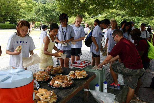 Children from the DEFY program eat sandwiches at Kintai park during a field trip Aug.5. The children are given sandwiches as a healthy alternative to fatty foods. The program shows the kids the importance of eating healthy, exercising and making the right choices.