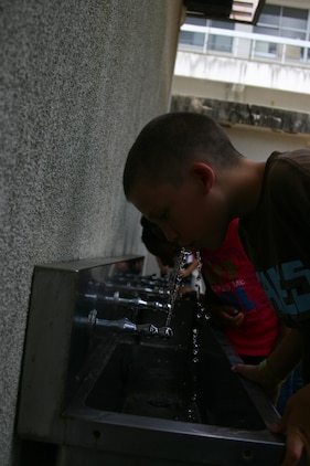 Children from the Youth and Teen center take a drink of fresh water recently purified at the Nishimi Water Treatment Plant. The water is inspected and must go through many tests before being ready to drink.