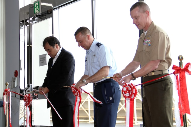 Masayoshi Tatsumi, Chugoku-Shikoku Defense Bureau director general (left), Col. Robert Ricci, 515 Air Mobility Operations Group commander and Col. James C. Stewart, station commanding officer, cut a ribbon at the Air Mobility Command passenger terminal here during the terminal's official opening ceremony here Aug. 19. Planning for construction started in 2001. Actual construction began in 2006 and finished in 2010.