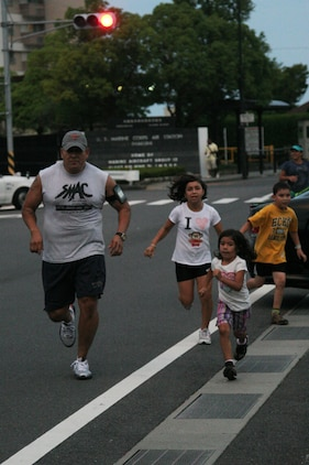 Staff Sgt. Carlos A. Calderon, an Iwakuni Roadrunner, runs with his children, Maria B. Calderon, 12 (left), Olivia M. Calderon, 5 (center), and Alex S. Calderon, 8 (right), as part of the Iwakuni Roadrunners outside the Marine Corps Air Station Iwakuni main gate here Aug. 24. The Roadrunners are a fitness club focused on getting runners out to share in the spirit of fitness.