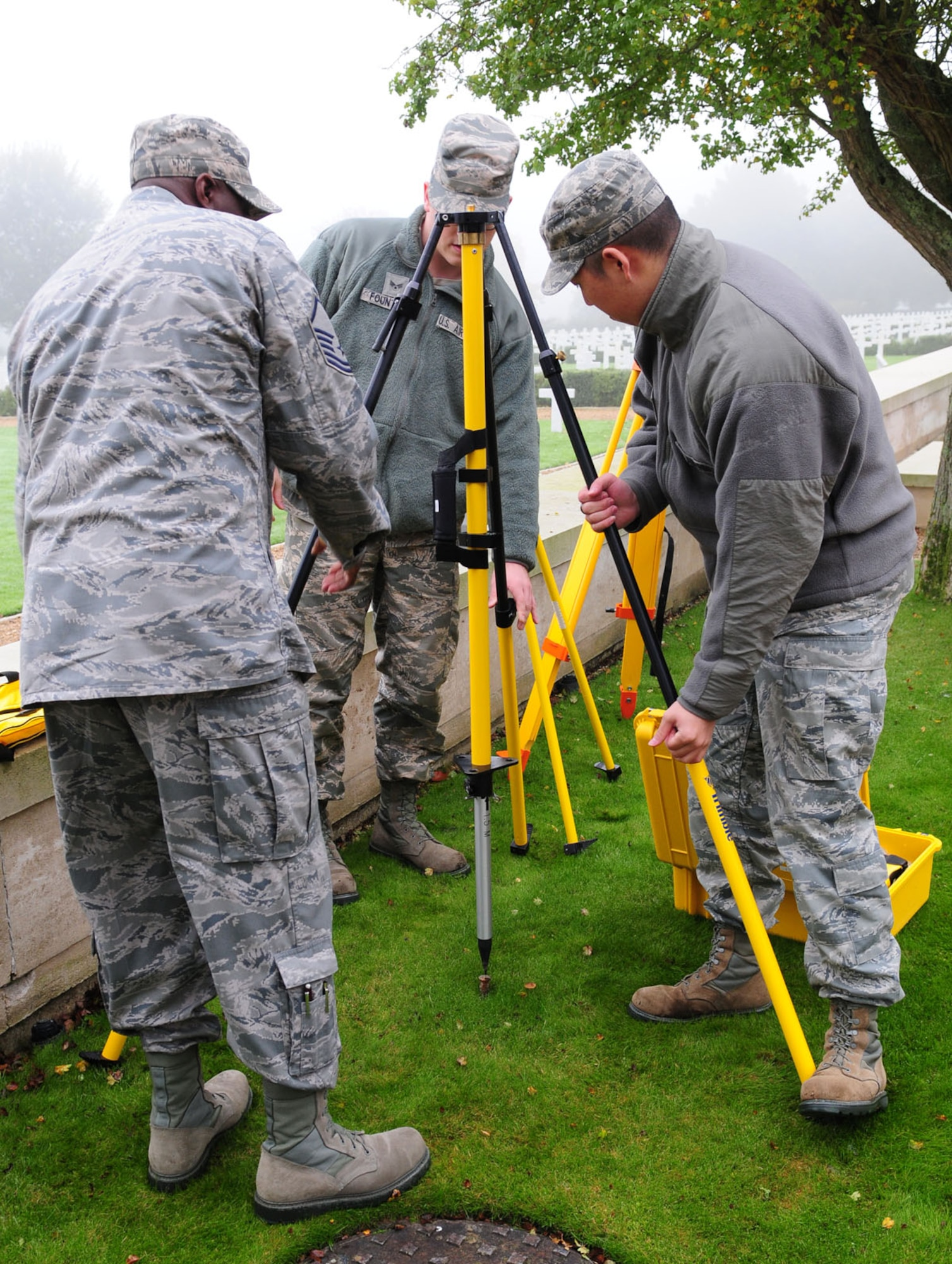 Master Sgt. Solomon Vincent, left,  assists Senior Airman Logan Fountaine, center, and Senior Airman Young Park, as they set up a quadpod ready to attach an antenna Oct. 16, 2013, at Madingley American Cemetery near Cambridge, England. The Airmen were taking GPS readings to annotate the exact location of each individual headstone. This equipment served as a base station, which collects data from 24 GPS satellites in orbit. All the data from the project will be made into an electronic map that allows families and friends of those lost in World War II to pinpoint the location of their resting place here.Vincent is a 100th Civil Engineer Squadron engineering flight superintendent and Fountaine and Park are 100th CES engineering flight journeyman.