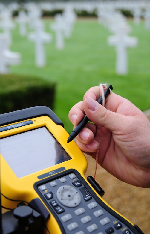 Senior Airman Logan Fountaine uses a data collector to input information and GPS grid coordinates Oct. 16, 2013, located at each headstone in Madingley American Cemetery, near Cambridge, England. The equipment was a base station to collect data from 24 GPS satellites in orbit. All the data from the project will be used to create an electronic map to allow families and friends of those Americans lost in World War II to pinpoint the location of their resting place. Fountaine is a 100th Civil Engineer Squadron engineering flight journeyman.