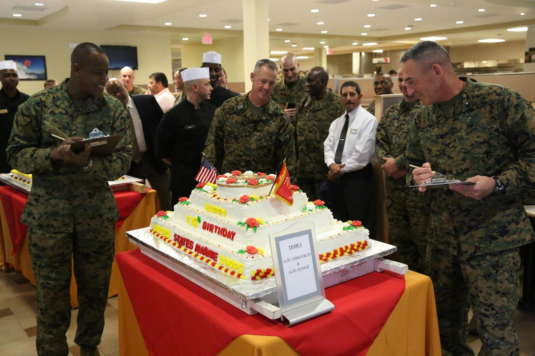 Brigadier Gen. James W. Lukeman, the 2nd Marine Division commanding general, Sgt. Maj. Bryan K. Zickefoose, the 2nd Marine Division sergeant major, and Master Gunnery Sgt. Anthony Butler, the food technician for G-4 Food Services observe a cake during the 2013 Marine Corps birthday cake competition aboard Marine Corps Base Camp Lejeune, Nov. 6, 2013. Food service Marines were tasked with creating a cake for celebrating the Marine Corps' 238th birthday.
