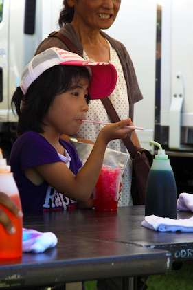 A young japanese child enjoys a cup of flavored shaved ice during the Summer Music Festival at the Torii Pines Golf Course here Saturday. Shaved ice was a popular treat served by many vendors at the festival.