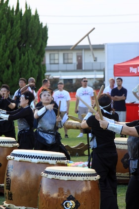 Members of Iwakuni Daiko pass sticks while performing a taiko drum routine during the Summer Music Festival Open House at the Torii Pines Golf Course here Saturday. Along with live music, Iwakuni Daiko and the Iwakuni Elite Tigers cheerleading team entertained the crowd with their performance routines.
