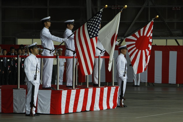 The color guard presents the colors while the Japanese and American national anthems play during the opening ceremony of the Japanese Maritime Self-Defense Force Iwakuni Air Base Festival here Sunday. JMSDF is tasked with the naval defense of Japan.