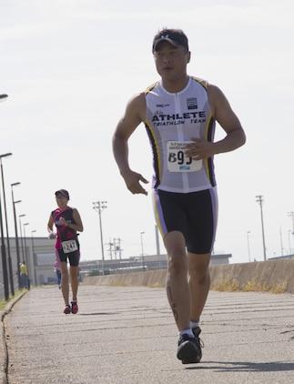 Tstuomu Morimoto, an experienced triathlon competitor, overtakes another triathlon competitor, during the Marine Corps Community Services Iwakuni Modified Triathlon here Sunday.