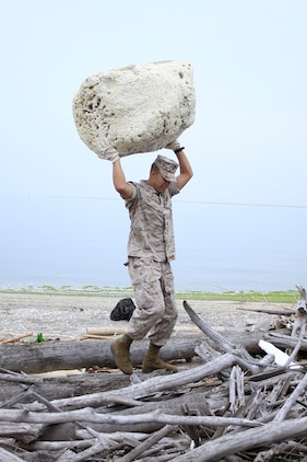 Lance Cpl. Jose Landaverdediaz, Combat Logistics Company 36 automotive organizational mechanic, carries a large piece of plastic foam over a pile of wood during a seawall clean-up near Penny Lake during an Earth Day celebration here April 22. More than 80 Marines, sailors and volunteers showed up to participate in the cleanup.