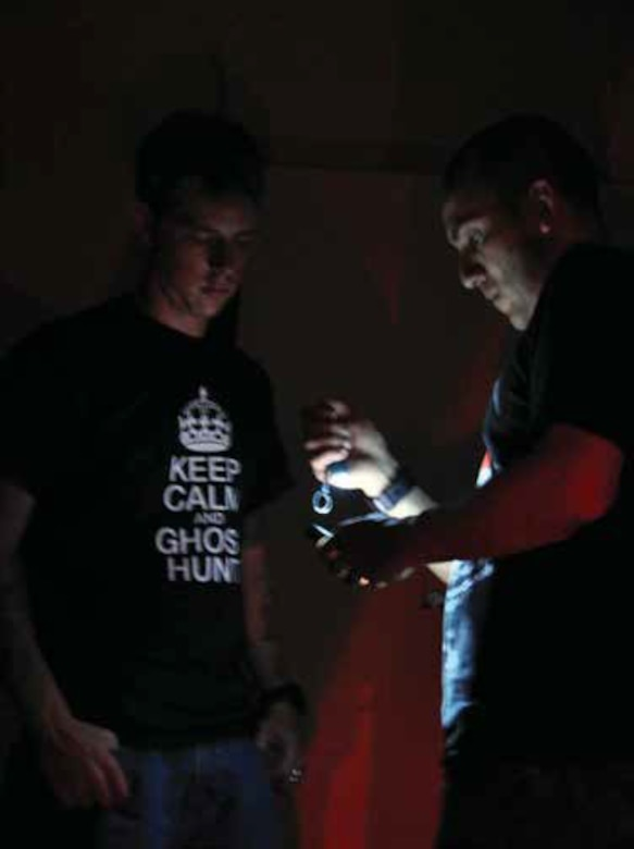 Senior Airman Mathieu Beaulieu, 912th Air Refueling Squadron (left) and Senior Airman Jose Mora, 452nd Aerospace Medicine Squadron, prepare to set up a digital voice recorder during a September 2013 paranormal investigation at March Air Reserve Base, Calif. Beaulieu, an active duty mechanic, and Mora, a Reserve medical administration technician, joined forces to investigate various locations on the historic base.(U.S. Air Force photo/Linda Welz)