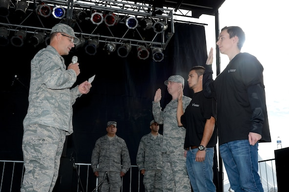 Col. Raymond A. Kozak (left), the 512th Airlift Wing commander at Dover Air Force Base, Del., administers the oath of enlistment to two new recruits and one reservist re-enlistee as part of the World Championship Punkin Chunkin Opening Ceremony in Bridgeville, Del., Nov. 2, 2013. The 512th AW, the only Air Force Reserve unit in Delaware, is actively hiring new people to meet a new recruiting goal to increase the size of the unit to more than 1,900 members. (Courtesy photo by Greg L. Davis)