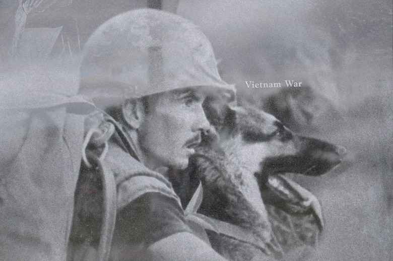 A image of a handler with his dog during the Vietnam War was part of collection that create a montage that is etched onto the face of the wall at the Military Working Dog Teams' National Monument which was revealed Oct. 28, 2013 at Joint Base San Antonio-Lackland, Texas. There was also a statue of an Airman that was accompanied by four dog statues. (U.S. Air Force photo by Airman 1st Class Krystal M. Jeffers/Released)