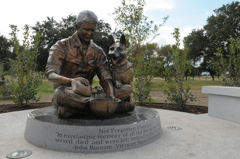 The Military Working Dog Teams' National Monument, which includes a statue of a handler with his dog, was revealed Oct. 28, 2013 at Joint Base San Antonio-Lackland, Texas. There was also a wall with a montage of images of handlers with their canines and a statue of an Airman that was accompanied by four dog statues. (U.S. Air Force photo by Airman 1st Class Krystal M. Jeffers/Released)