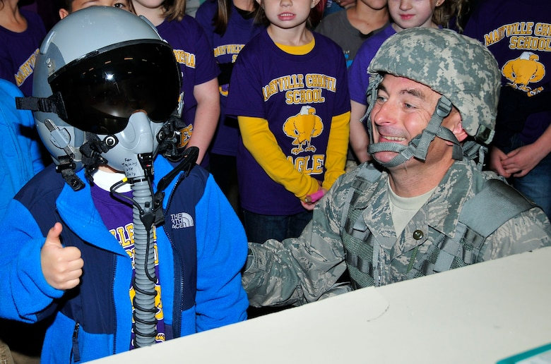 Tech. Sgt. Jon Crawford, 134 ARW Aircrew Flight Equipment Specialist, smiles as Caden Jones, a Maryville Christian School 1st grader, gives a thumbs up while wearing pilot training gear.  Caden's father, Master Sgt. Eric Jones, is a Boom Operator with the 134th Air Refueling Wing.  (U.S. Air National Guard photo by Master Sgt. Kendra M. Owenby, 134 ARW Public Affairs)