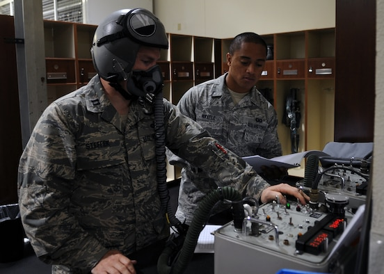U.S. Air Force Airman 1st Class Pesamino Mikaele, right, assists Capt. Craig Steffak, both from the 7th Operations Support Squadron, with pre-flighting his flight helmet and mask Oct. 29, 2013, at Dyess Air Force Base, Texas. This procedure ensures aircrew member's microphone works correctly and the oxygen mask fits properly prior to flight. (U.S. Air Force photo by Senior Airman Shannon Hall/Released)