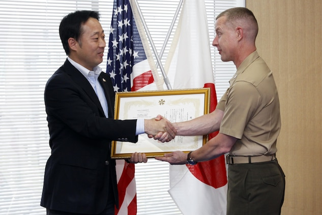 Yoshihiko Fukuda, Iwakuni city mayor, presents Col. James C. Stewart, station commanding officer, with a letter of appreciation at the Iwakuni cityhall, June 13, for the station's contribution during Operation Tomodachi. Operation Tomodachi was the joint relief effort conducted by the U.S. and Japanese government to help the victims of the 9.0 magnitude earthquake and tsunami that shook northern Japan March 11.