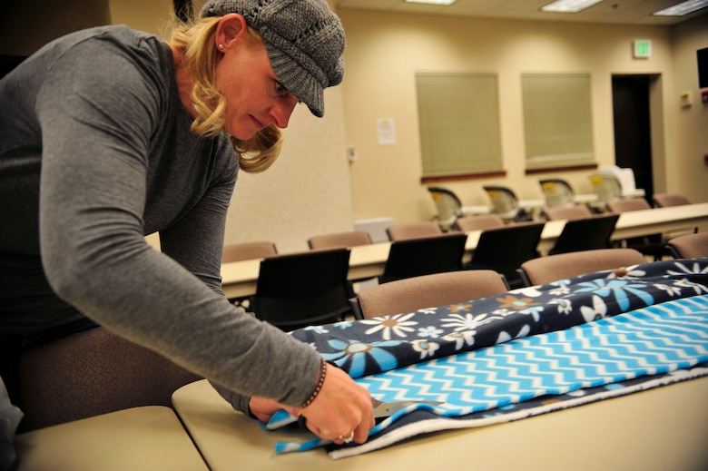 A volunteer cuts patterned fleece Nov. 7, 2013, at the chapel on Buckley Air Force Base, Colo. The Women's Empowerment Group, Buckley Spouses and Buckley Women's Ministry, along with women from all over the base, joined together to create blankets to donate to the Comitis Crisis Center in Aurora, Colo. (U.S. Air Force Airman 1st Class Samantha Saulsbury/Released)