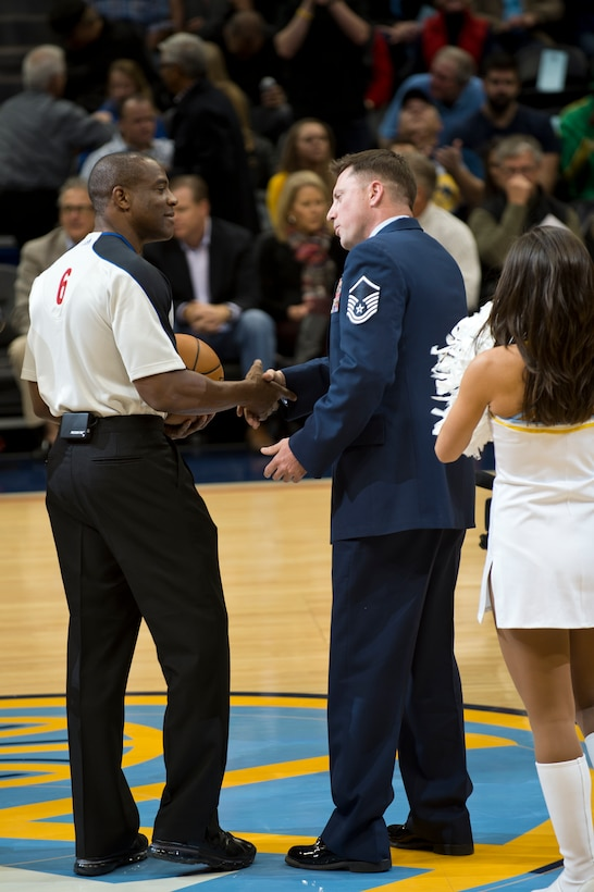 Master Sgt. Ed Schlade, 460th Space Communications Squadron, delivers the game ball to the referee at the Denver Nuggets vs. Atlanta Hawks game Nov. 7, 2013, at the Pepsi Center in Denver. The Nuggets showed their military appreciation by honoring several Airmen at the game. (U.S. Air Force photo by Senior Airman Riley Johnson/Released)