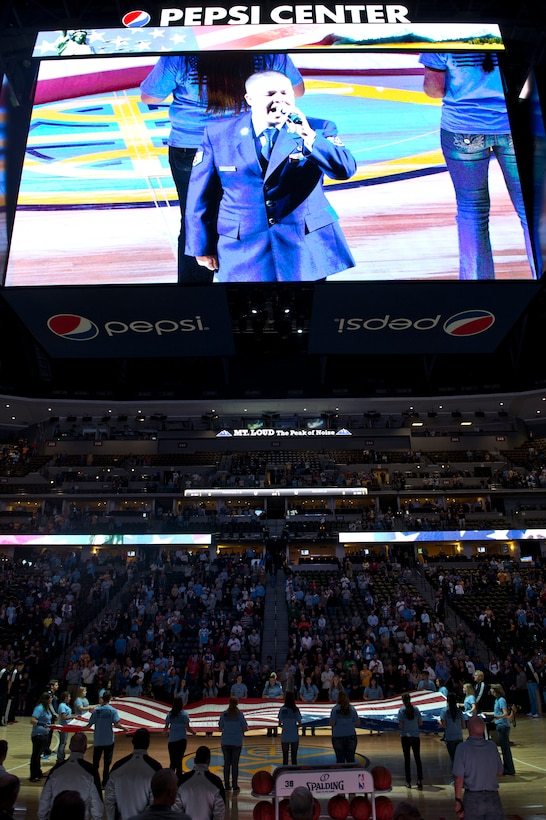 Staff Sgt. Zachery Rayburn, 460th Space Communications Squadron, sings the national anthem at the Denver Nuggets vs. Atlanta Hawks game Nov. 7, 2013, at the Pepsi Center in Denver. In 2011, Rayburn was a singer in the Tops in Blue, an Air Force touring ensemble of musicians and performers. (U.S. Air Force photo by Senior Airman Riley Johnson/Released)