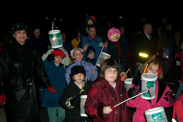 """SPANGDAHLEM AIR BASE, Germany-- Local children carry colorful lanterns as they march through the streets of Spangdahlem village in a past Saint Martin procession. This year, parades are scheduled to take place tonight through next week with the dates and times varying from town to town. In some towns, firefighters lead the parade with torches in hand, followed by the town band and a man portraying St. Martin, clad in the uniform of a Roman legionnaire, on horseback. The colorfully illuminated processions end with a huge bonfire. """"St. Martin"""" then encourages the children and hands out large sugar pretzels. The Saint Martin parade is a perfect event for small children with their parents. Local villages invite the American neighbors to participate in this traditional local event. (U.S. Air Force photo by Iris Reiff)"""