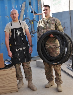 Tech. Sgt. Juan Sanchezduarte (left) and Senior Airman Mark Zorich (right), both assigned to the 451st Expeditionary Logistics Readiness Squadron, pose with some bicycle tires outside Tan Box Bike Repair at Camp Losano, Kandahar Airfield, Afghanistan, Nov. 11, 2013. Both Airmen volunteer their time and resources so service members at KAF can have free bicycle repairs available. (U.S. Air Force photo by Capt. Jason Smith)