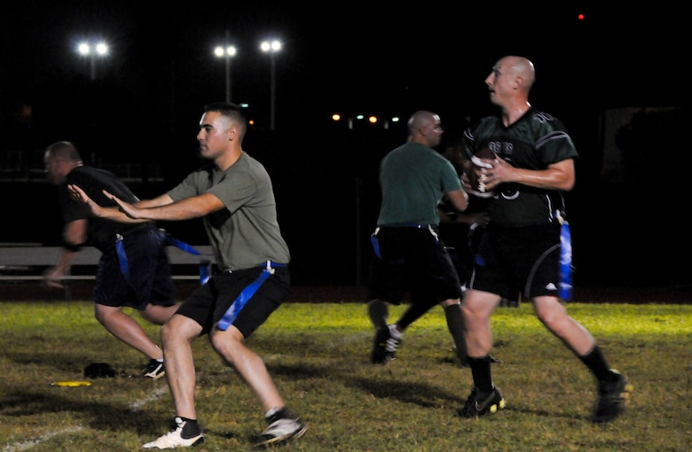 A member from the 36th Civil Engineer Squadron prepares to pass the ball to a teammate during an intramural football game against the 94th Army Air and Missile Defense Command Nov. 6, 2013, on Andersen Air Force Base, Guam. The 36th CES defeated the 94th AAMDC 18-14. (U.S. Air Force photo by Airman 1st Class Amanda Morris/Released)