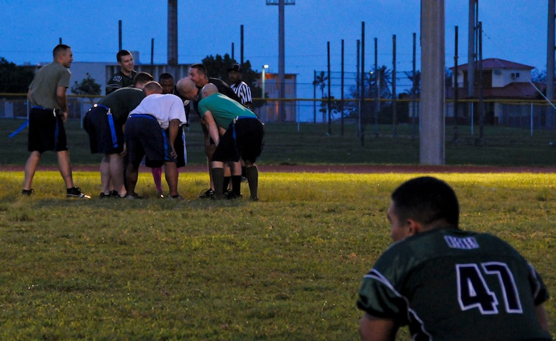Members of the 36th Civil Engineer Squadron intramural flag football team huddle to decide a game plan for the game against the 94th Army Air and Missile Defense Command Nov. 6, 2013, on Andersen Air Force Base, Guam. The 36th CES defeated the 94th AAMDC 18-14. (U.S. Air Force photo by Airman 1st Class Amanda Morris/Released)