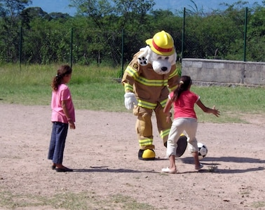 Sparky the Fire Dog plays soccer with children at the Nuestra Seniora de Guadalupe orphanage in Comayagua, Honduras, Nov. 6, 2013.  Twenty-one members of the 612 ABS spent the afternoon at orphanage.  Six children at the orphanage had a birthday during the month of November, and the 612 ABS members brought along birthday gifts to celebrate the occassion.  Members of the 612th spent the afternoon playing and visiting with the children.  (U.S. Air Force photo by Tech. Sgt. Stacy Rogers)