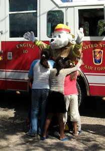 Sparky the Fire Dog greets children at the Nuestra Seniora de Guadalupe orphanage in Comayagua, Honduras, Nov. 6, 2013.  Twenty-one members of the 612 ABS spent the afternoon at orphanage.  Six children at the orphanage had a birthday during the month of November, and the 612 ABS members brought along birthday gifts to celebrate the occassion.  Members of the 612th spent the afternoon playing and visiting with the children.  (U.S. Air Force photo by Tech. Sgt. Stacy Rogers)