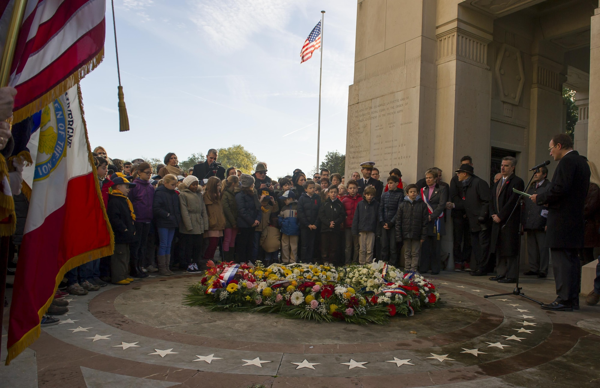 People listen to the closing remarks of a Veteran's Day ceremony at the Lafayette Escadrille memorial in Marnes-la-Coquette, France Nov. 11, 2013. Lafayette Escadrille was a French Air Service squadron during World War I comprised largely of volunteer American fighter pilots.