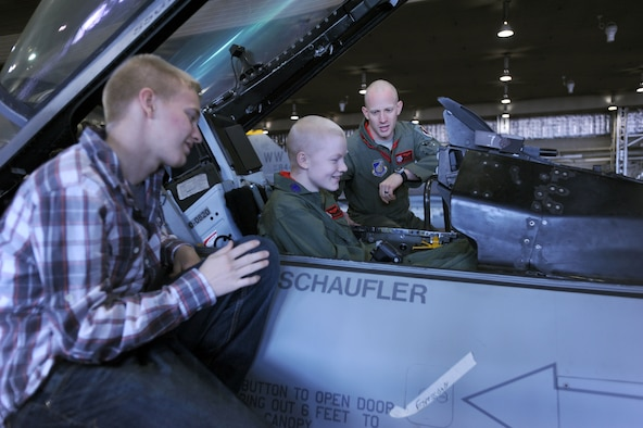Capt. Jonathan Kay, 13th Fighter Squadron fighter pilot (right), explains an F-16CJ cockpit to 17-year-old Jonah Skrove (center), and his brother Airman 1st Class Jared Skrove (left)Nov. 1, 2013 at Misawa Air Base, Japan. Diagnosed with osteosarcoma last fall, Jonah was given the opportunity through the Make-A-Wish Foundation to do anything or go anywhere he wanted. Jonah wished to visit his brother here, and was treated to a tour of several base agencies during his visit. Jonah Skrove is a 13th Aircraft Maintenance Unit electrical and environmental maintenance specialist.