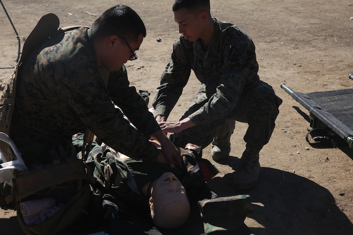 Seaman Daniel Benavidas, left, a logistics specialist, and Lance Cpl. Joshua Shed, right, a warehouse clerk, both with 1st Supply Battalion, Combat Logistics Regiment 15, 1st Marine Logistics Group, treat a victim with a gunshot wound during a combat lifesavers course aboard Camp Pendleton, Calif., Nov. 6, 2013. During the course, Marines and sailors learned vital techniques such as providing CPR, treating injuries like sucking chest wounds and applying tourniquets.