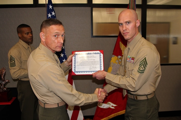 Gunnery Sgt. Raymond Jentz (right) accepts the Eugene M. Stoner Award from Brig. Gen. Frank Kelley, commander of Marine Corps Systems Command, Nov. 4 on Hospital Point at Marine Corps Base Quantico, Va. Jentz is a project officer for the Radio Reconnaissance Equipment Program in MCSC's Marine Intelligence. The Stoner Award is presented to a Marine Corps staff noncommissioned officer for superior professional excellence and innovation in pursuit of the acquisition, fielding and support of systems and equipment to the operating forces.